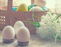 Canestro con le uova di Pasqua dipinte e un mazzo dei fiori bianchi immagini stock libere da diritti