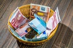 Canestro con soldi dalle donazioni Fotografie Stock Libere da Diritti