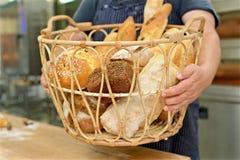 Canestro della tenuta del panettiere di pane nella cucina del forno fotografia stock