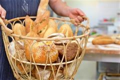 Canestro della tenuta del panettiere di pane nella cucina del forno fotografie stock