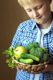 Canestro della tenuta del ragazzo con le verdure verdi Fotografie Stock