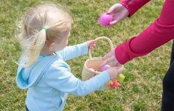 Canestro della tenuta della ragazza alla caccia all'aperto dell'uovo di Pasqua immagini stock libere da diritti
