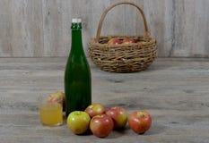 Canestro di Apple e bottiglia di sidro. immagine stock