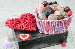 Canestro di Candy, biscotti e cuore decorativo di giorno del ` s del biglietto di S. Valentino sulla vecchia scatola Fotografie Stock Libere da Diritti