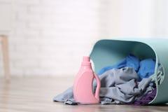 Canestro di lavanderia e del detersivo con i vestiti sporchi sul pavimento all'interno immagini stock