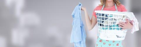 Canestro di lavanderia più pulito della tenuta con fondo luminoso Fotografia Stock