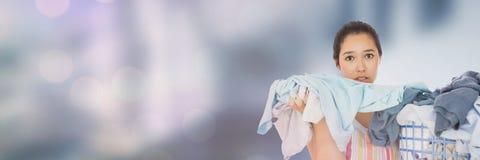 Canestro di lavanderia più pulito della tenuta con fondo luminoso Immagine Stock