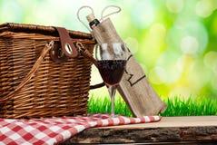 Canestro di picnic sulla tavola con bicchiere di vino Immagini Stock Libere da Diritti
