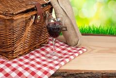 Canestro di picnic sulla tavola e sulla bottiglia dell'angolo superiore del vino Fotografie Stock
