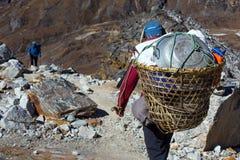 Canestro di trasporto del portatore nepalese con il prodotti per la casa rurale Immagine Stock