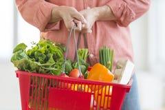 Canestro di trasporto dell'uomo in pieno delle verdure Fotografie Stock