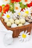 Canestro di vimini con le uova di Pasqua, i fiori ed il coniglio bianco Fotografie Stock