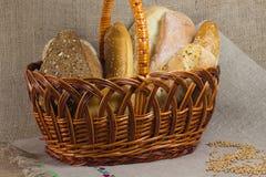 Canestro di vimini con pane I grani di grano su tablecl tessuto Fotografie Stock Libere da Diritti