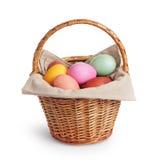 Canestro di vimini in pieno delle uova di Pasqua di colori pastelli Fotografia Stock
