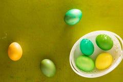 Canestro dipinto delle uova di Pasqua sui vecchi precedenti di legno Fotografie Stock