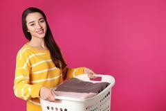 Canestro felice della tenuta della giovane donna con la lavanderia sul fondo di colore fotografia stock