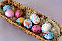 Canestro ovale in pieno delle uova di Pasqua brillantemente colorate fotografie stock libere da diritti