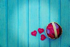 Canestro pieno con i cuori su un fondo di legno blu Fotografie Stock