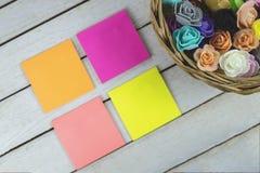 Canestro in pieno dei fiori di carta e delle note appiccicose di carta vuote con lo spazio della copia per testo Fotografia Stock