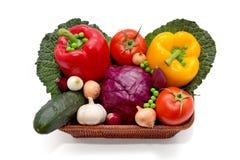 Canestro in pieno dei peperoni, della cipolla, dell'aglio, del cetriolo, del cavolo, dei piselli, dei pomodori e del cavolo Immagine Stock