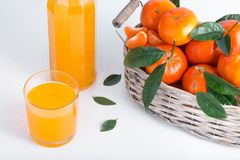 Canestro pieno del mandarino con un vetro di succo immagini stock