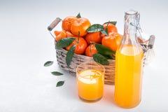 Canestro pieno del mandarino con un vetro di succo immagini stock libere da diritti