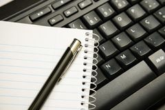 Pen and notebook on computer keyboard. Image to represent normal work in the office or at home royalty free stock images