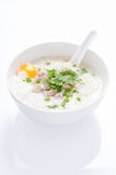 Cangee or rice gruel. With minced pork and egg in white bowl and spoon on white background and reflection Stock Photos