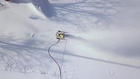 Canhão da neve que trabalha na montanha do esqui na opinião do zangão do recurso do inverno Canhão da neve da vista aérea na ação vídeos de arquivo