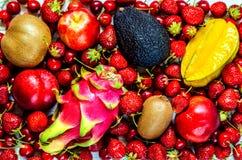 Canhão maduro do fruto, pêssego, abacate, fruto do dragão entre bagas das morangos e cerejas doces imagens de stock royalty free