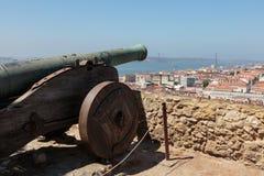 Canhão velho em Castelo de Sao Jorge, opinião aérea Lisboa e 25a April Bridge, Portugal Imagens de Stock