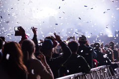 Canhões dos confetes que jogam confetes sobre a multidão partying Fotografia de Stock Royalty Free