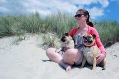 Cani e proprietario del carlino su una spiaggia soleggiata Immagini Stock