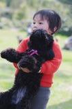 Caniche del abrazo del niño Imagenes de archivo