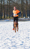 Canicross running in snow Royalty Free Stock Photos