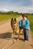 Canine friend. The little boy with a dog on rural road Stock Photo