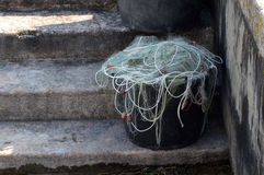 Canister with fishing net. On concrete steps Stock Photography