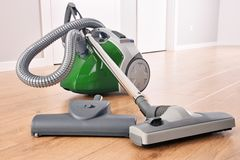 Canister vacuum cleaner for home use on the floor panels. In the apartment royalty free stock image