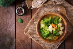 Canja de galinha com brócolis, as ervilhas verdes, as cenouras e o aipo Imagem de Stock