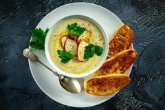 A canja de galinha cremosa com os vegetais na bacia com brinde do chiabatta, a salsa e as sementes do nigela polvilham na tabela  Imagens de Stock