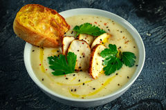 A canja de galinha cremosa com os vegetais na bacia com brinde do chiabatta, a salsa e as sementes do nigela polvilham na tabela  Fotografia de Stock