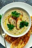 A canja de galinha cremosa com os vegetais na bacia com brinde do chiabatta, a salsa e as sementes do nigela polvilham na tabela  Fotos de Stock Royalty Free