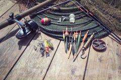 Canna da pesca, bobina, galleggianti e fondo dell'attrezzatura fotografia stock libera da diritti