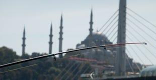 Canna da pesca davanti al contesto deliberatamente vago di una moschea con la cupola ed i minareti immagini stock libere da diritti