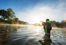 Canna da pesca della tenuta del pescatore, stante nel fiume fotografia stock libera da diritti