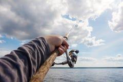 Canna da pesca a disposizione su un fondo di un cielo nuvoloso Immagine Stock Libera da Diritti