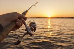 Canna da pesca a disposizione sul fondo di tramonto Fotografia Stock Libera da Diritti