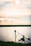 Canna da pesca nel bello tramonto al bordo del lago Fotografia Stock