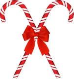 Canna di caramella rossa brillante di Natale con l'arco Fotografia Stock Libera da Diritti