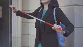 Canna per i ciechi nelle mani di giovane donna alla moda sulla via fotografia stock